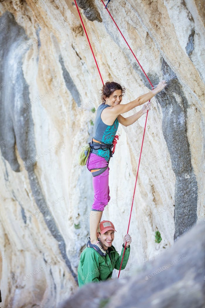 Female rock climber standing on shoulders of her partner