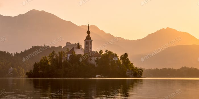 Island with church in lake Bled on orange hazy morning