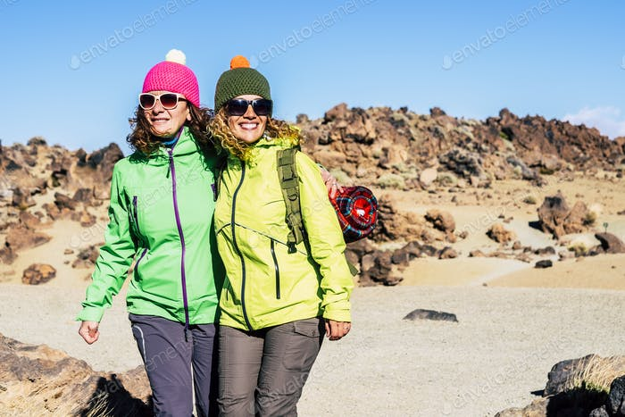 Couple of people women friends enjoying together the outdoor leisure sport activity hiking