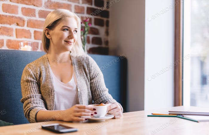 Relaxed woman drinking coffee in a cafe.