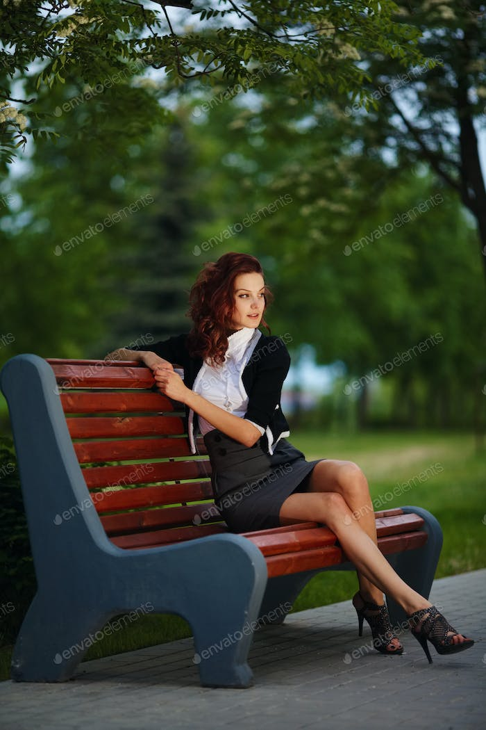 beautiful girl sitting on bench in park
