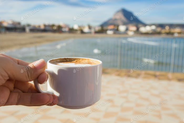 Cup of coffee in hand on the background of a beautiful beach