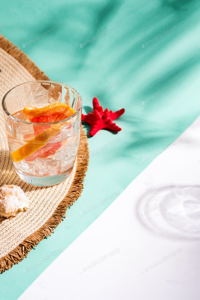 Thumbnail for Creative summer backdrop from wide-brimmed hat and glass of refreshing cold citrus cocktail on a