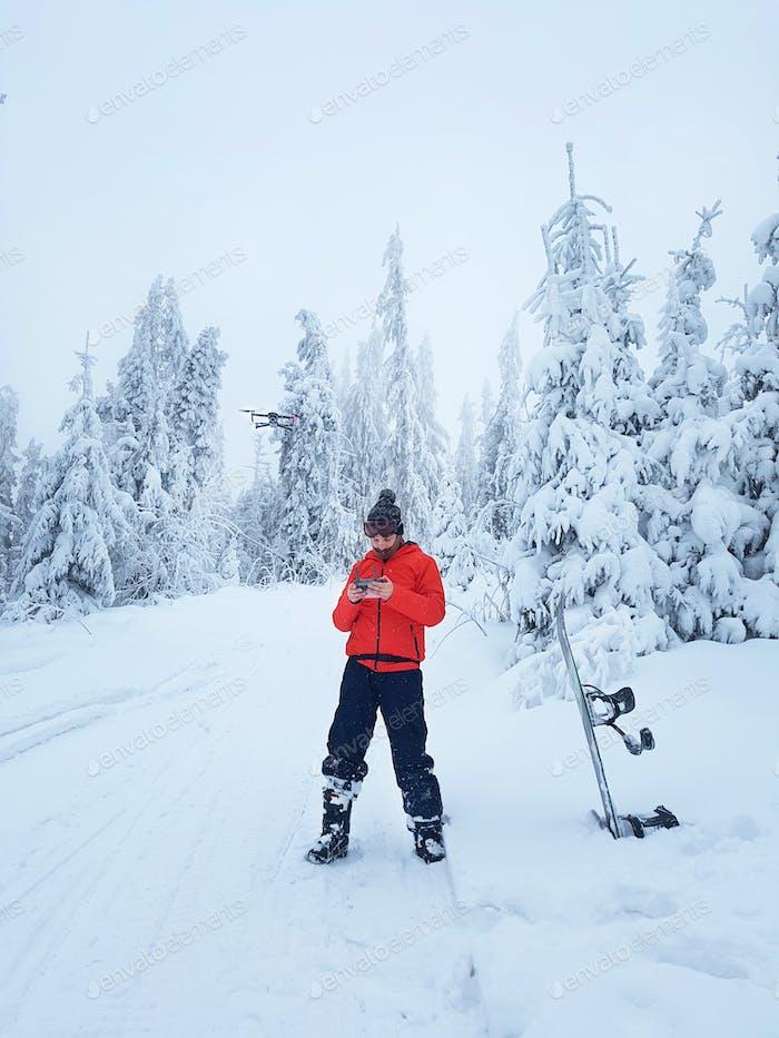 Snowboarder steuert die Drohne während einer Pause im Skaten