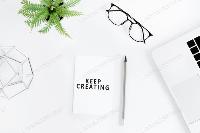 flat lay with Keep creating motivational quote on modern workplace with laptop