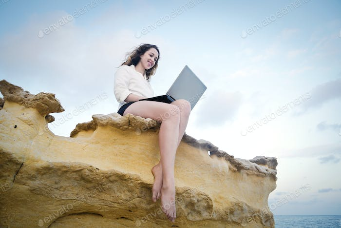 Girl on the rocks with a laptop