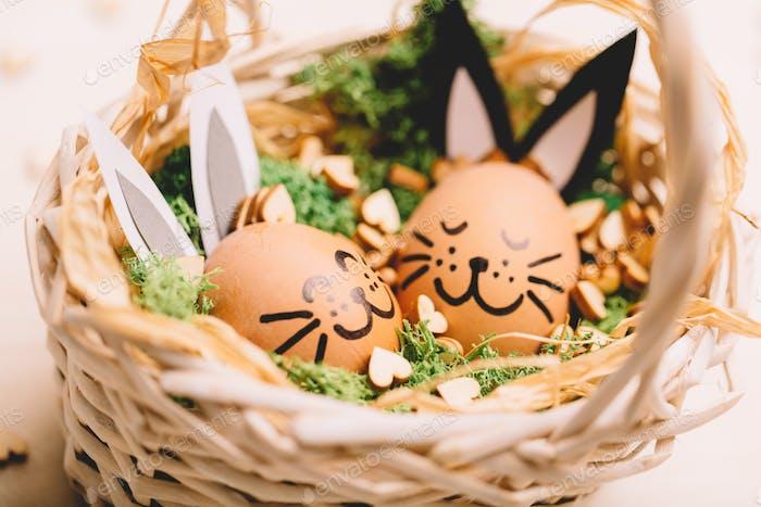 Zwei lächelnde Eierhasen liegen in den Korb.