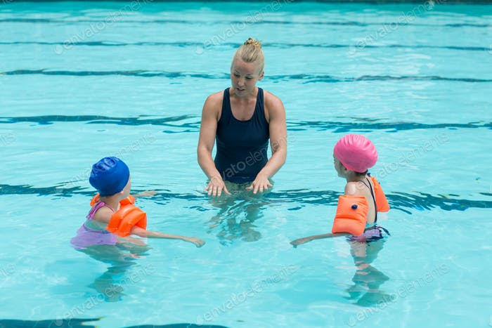 Female instructor assisting children in swimming pool
