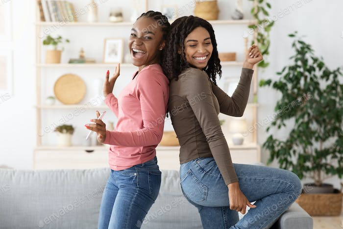 Cheerful black girlfriends singing and dancing at home