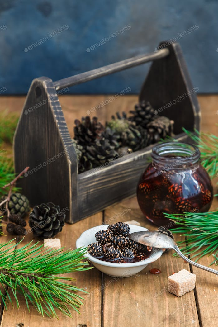 Pine cones jam in jar with wooden box
