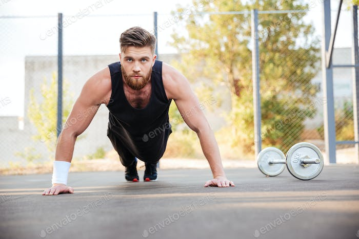 Portrait of a concentrated man athlete doing plank exercise outdoors