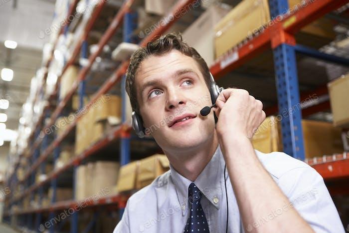 Geschäftsmann mit Headset im Distributionslager