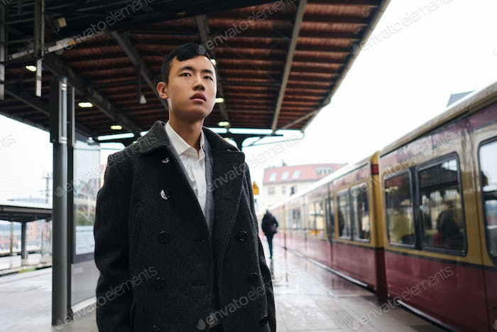 Young stylish Asian businessman intently looking away while waiting train on subway platform