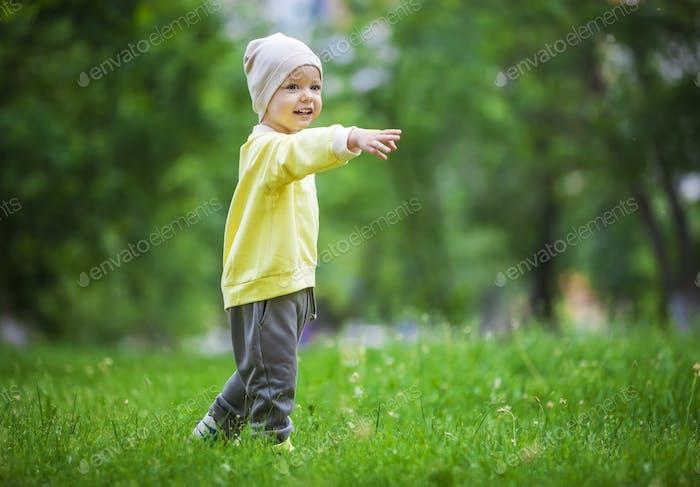 Porträt eines glücklichen kleinen Jungen zeigt auf etwas im Freien