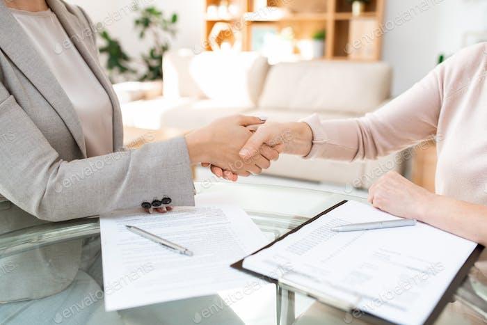 Handshake über Tisch von jungen und reifen Weibchen nach Verhandlungen