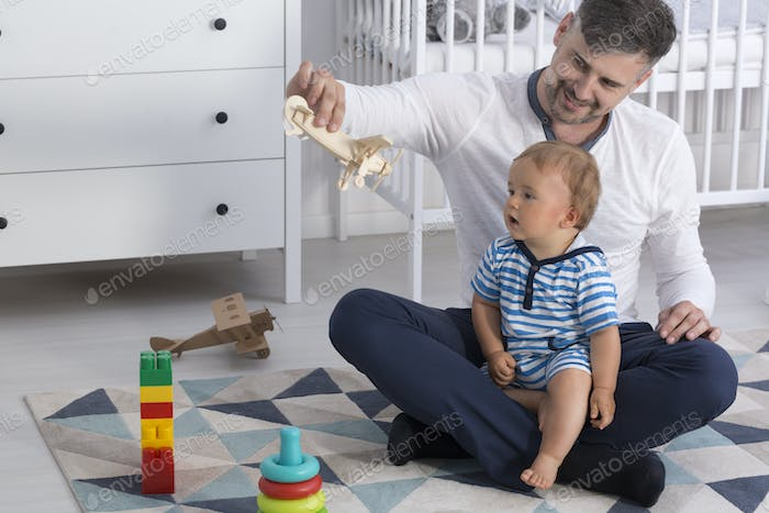 Father showing child a wooden plane