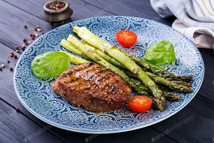 Barbecue grilled beef steak meat with asparagus and tomato.