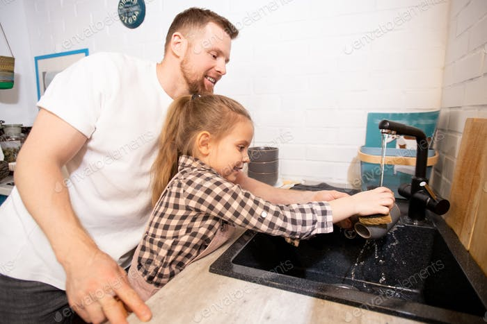 Happy young affectionate father helping his little daughter to wash her mug