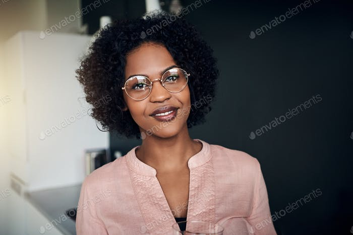 Confident African businesswoman standing in a modern office