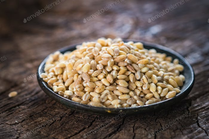 Dry pearl barley on rustic background