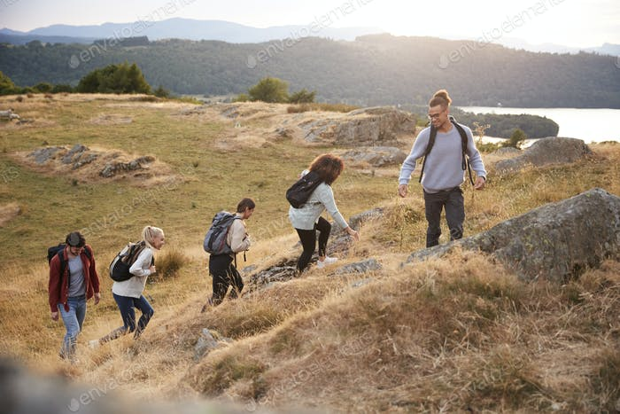 A multi ethnic group  of five young adult friends smile while climbing to the summit