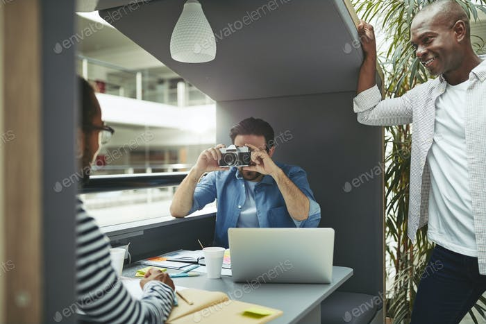 Designer taking a colleague's photo in an office meeting pod