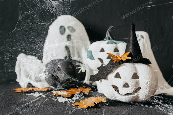 Happy halloween holiday. Halloween decorations, black and white pumpkins, bats, ghosts on a black