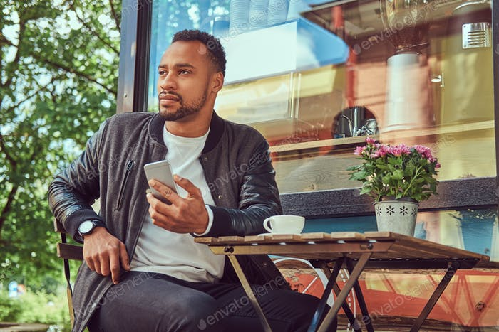 Fashionable African-American bearded man sitting at a coffee shop outdoors