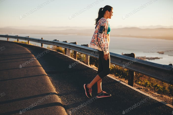 Fitness female athlete standing outdoors looking at a view