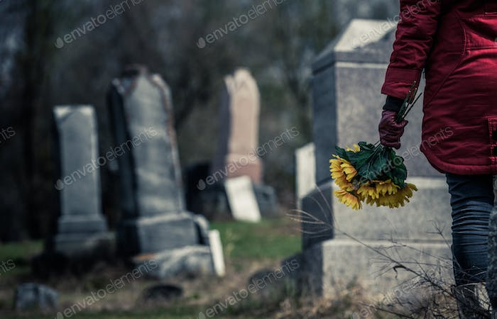 Close-up of a Sad in front of a Gravestone.