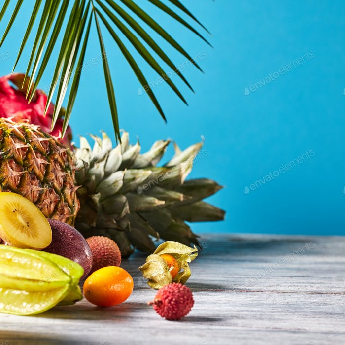 Various juicy exotic fruits - lychee, pineapple, carambola, litchi, dragon fruit on a gray wooden