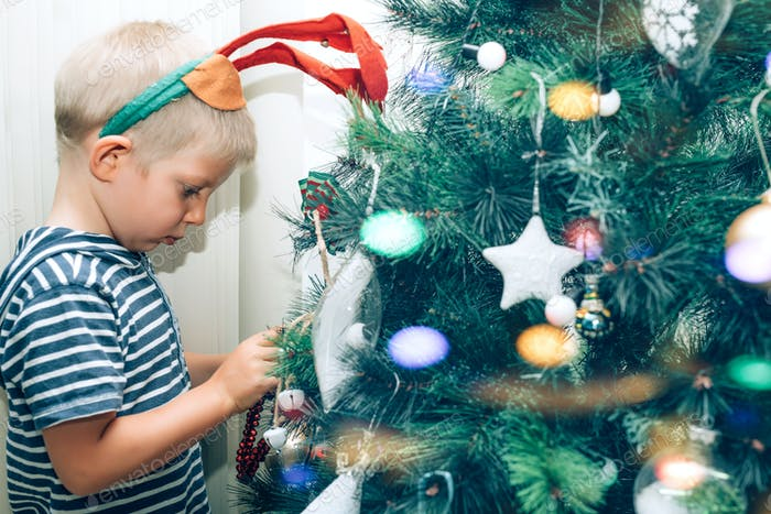 Cute little kid with deer antlers on the head decorating Christmas tree