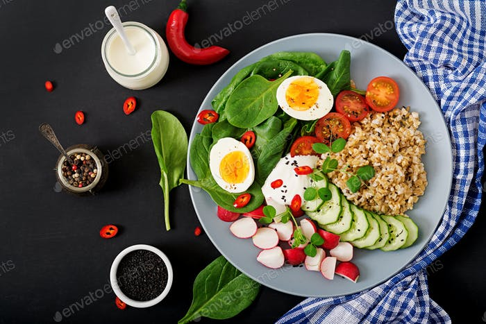 Diet menu. Healthy salad of fresh vegetables - tomatoes, cucumber, radish, egg, spinach