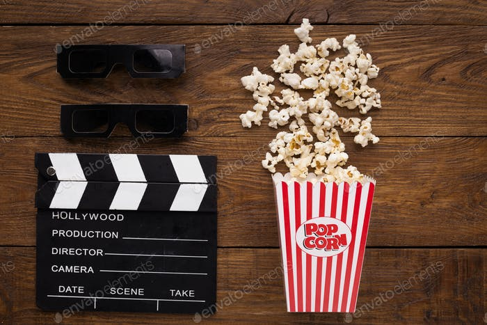 Clapperboard, 3D glasses and popcorn on wooden background
