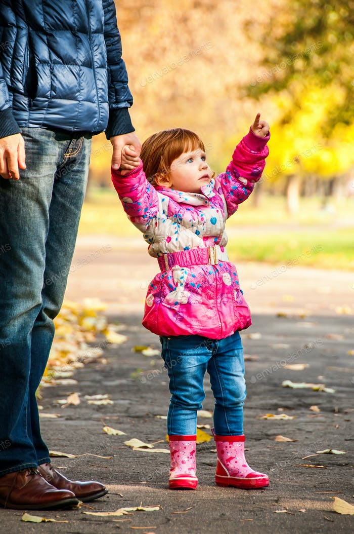 Little girl walks with my dad, pointing to something in the park
