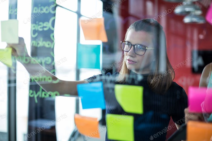 Business executive sticking sticky notes on glass