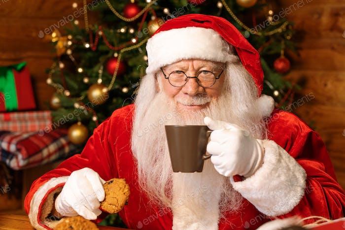 Happy Santa with mug of hot tea having drink and eating tasty homemade cookies