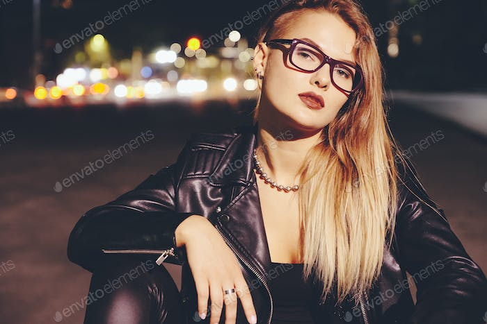 Sexy woman with long hair in leather clothes on night city lights background