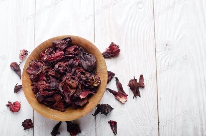 Top view at wooden bowl of dry hibiscus petals on white backgrou
