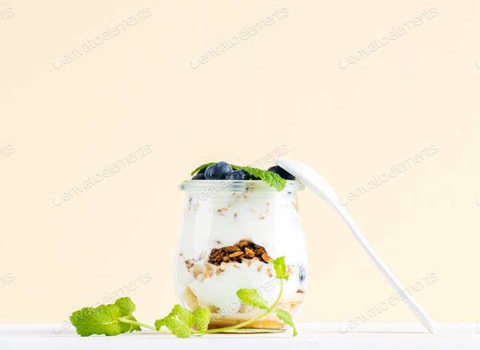 Yogurt oat granola with jam, blueberries and green leaves in glass jar on pastel yellow backdrop.