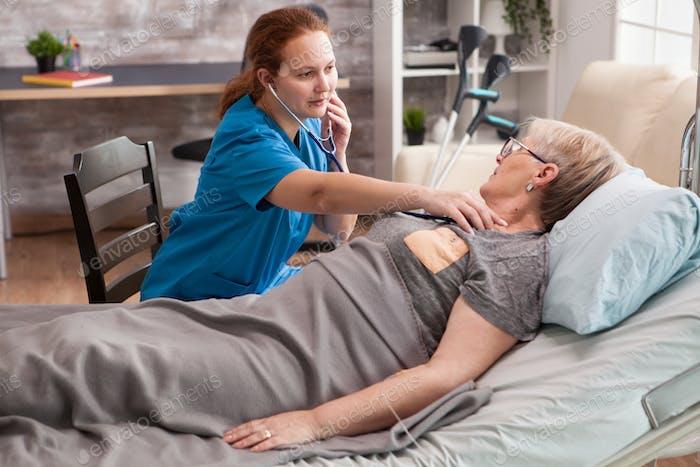 Female nurse in nursing home doing hear beat mesasurement