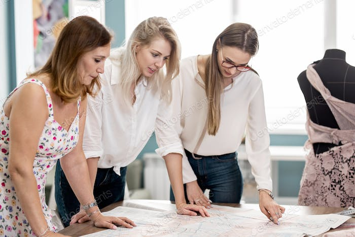 Three smart-looking pretty women are pointing at the cutting-out. Fashion, tailor's workshop