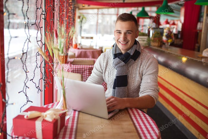 Smiling young man with laptop