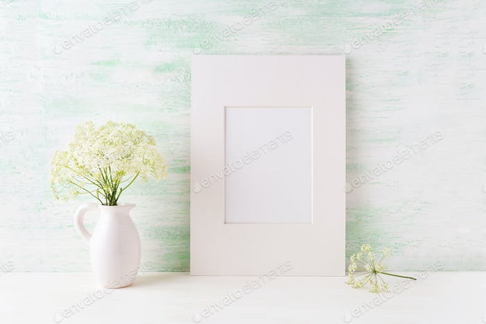 Easy white frame mockup with tender wild flowers in pitcher