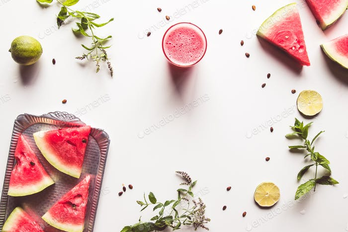 Red slices of ripe watermelon with mint leaves and lime slices on a white background