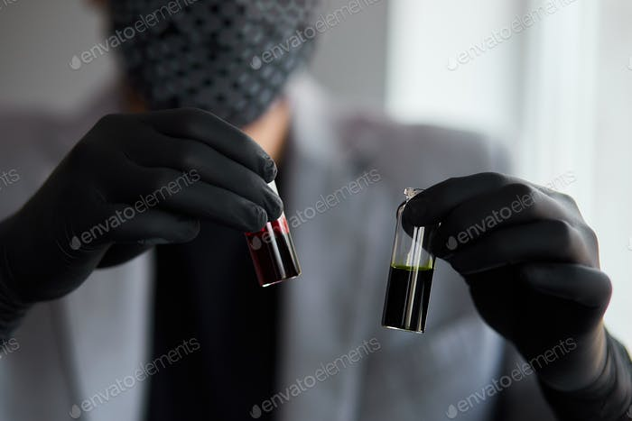Young man holding test tubes with blood and antidote in his hand. Coronavirus blood Test tube.