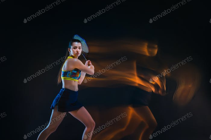 Portrait of beautiful girl tennis player with a racket on dark background