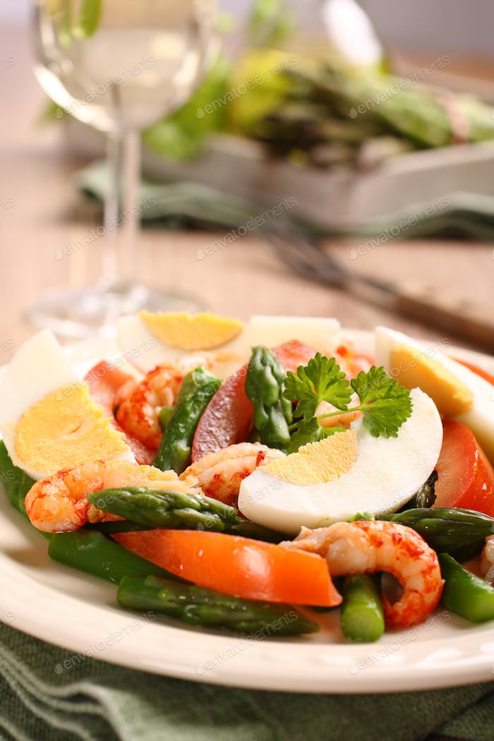 Fresh salad with asparagus, eggs, shrimp and tomatoes