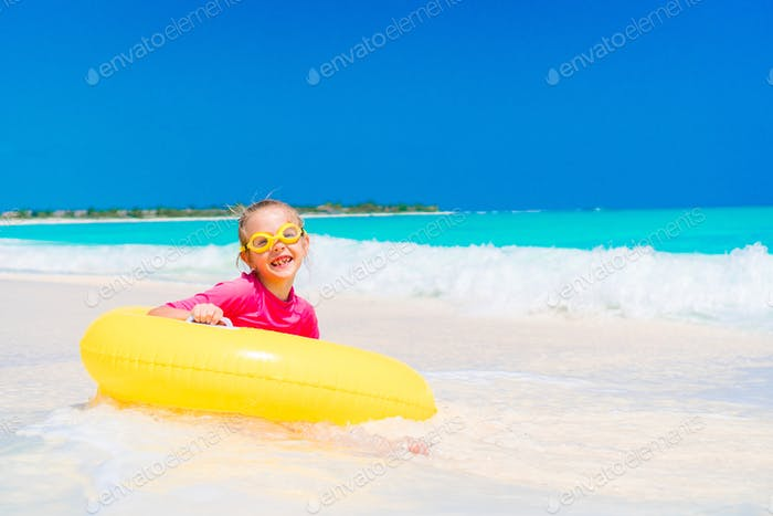 Adorable little girl with inflatable rubber circle splashing. Kid having fun on summer active