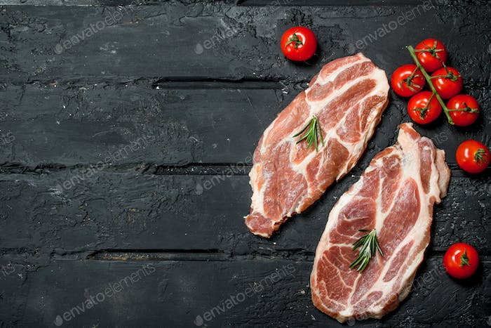 Raw pork steaks with tomatoes and rosemary.